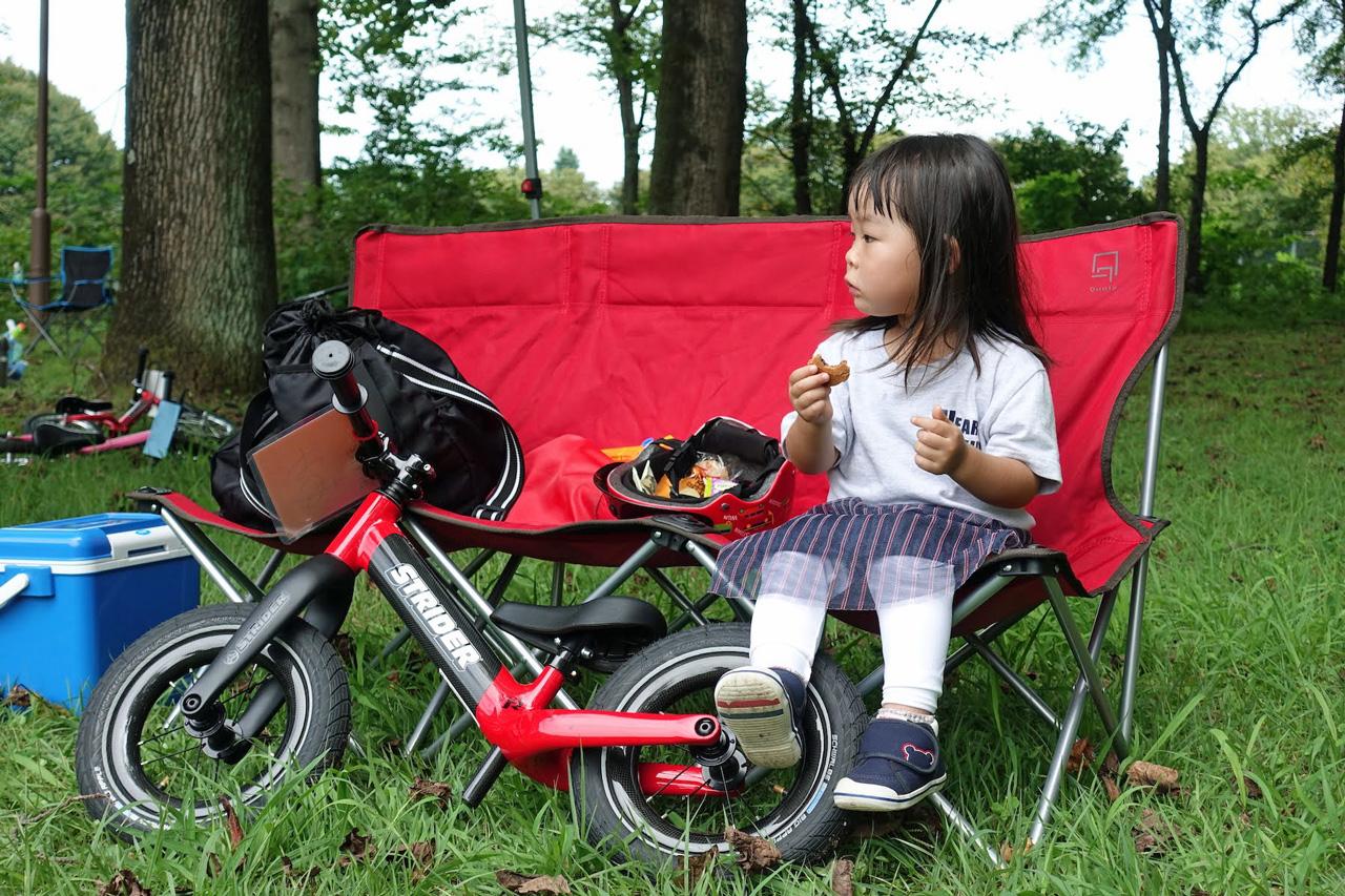 アウトドアベンチに座ってお菓子を食べるストライダーキッズ