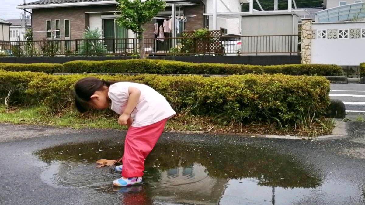 レインウェアを着て水たまりで遊ぶ女の子