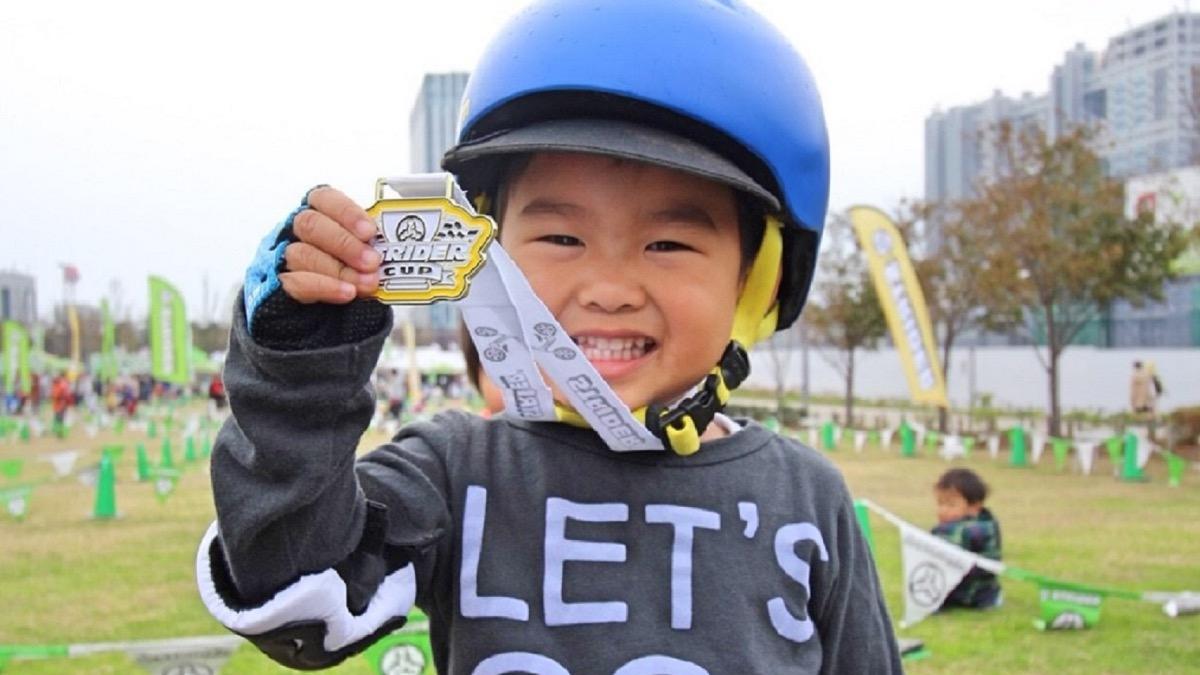 ストライダーカップのメダルを持って笑顔の男の子