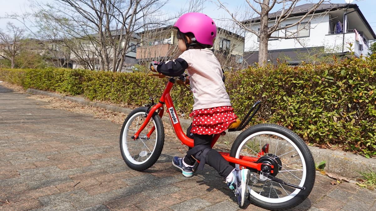 ペダルなし自転車を足で蹴って走り出す女の子