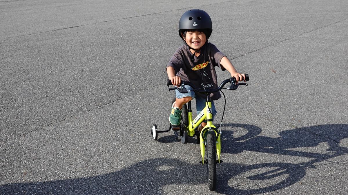 トリプルエイトのヘルメットをかぶり、補助輪付きのストライダー14xに乗る男の子