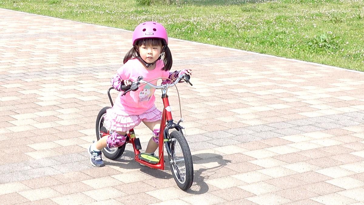 ヘルメットとプロテクターを装着してキックルに乗る女の子
