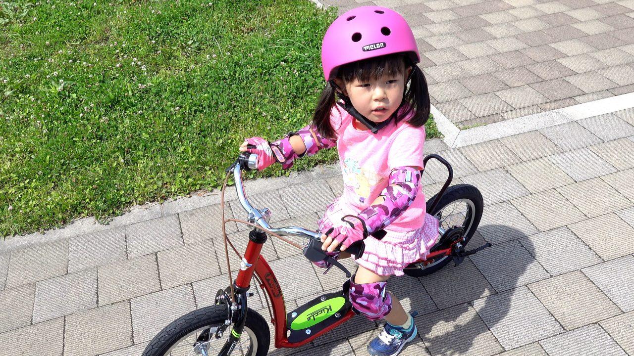 ヘルメットとプロテクターを装着し、キックルに乗る4歳の女の子