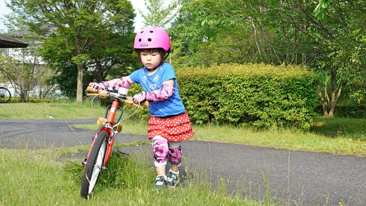 ヘルメットとプロテクターを付けてケッターサイクルを押す4歳の女の子
